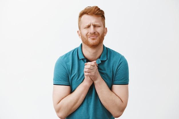 Homem ruivo e branco com cerdas em uma camiseta verde, fechando os olhos e franzindo a testa, apertando as mãos sobre o peito enquanto implora por algo apaixonadamente