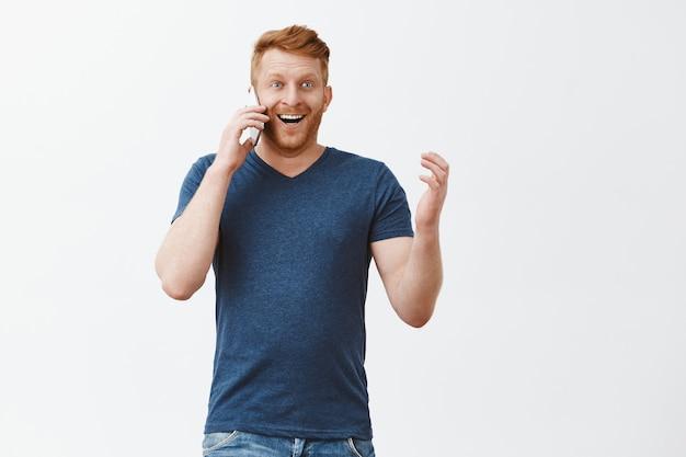 Homem ruivo emocionado e feliz surpreso com cerdas segurando o smartphone perto da orelha, falando com um sorriso satisfeito e surpreso, gesticulando sobre a parede cinza