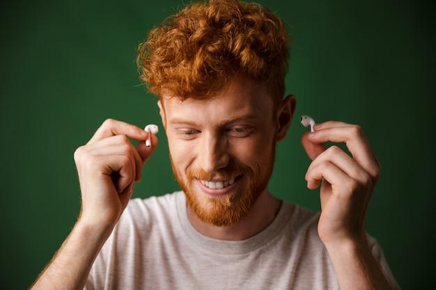 Homem ruivo encaracolado bonito em t-shirt branca inserir fones de ouvido nos ouvidos