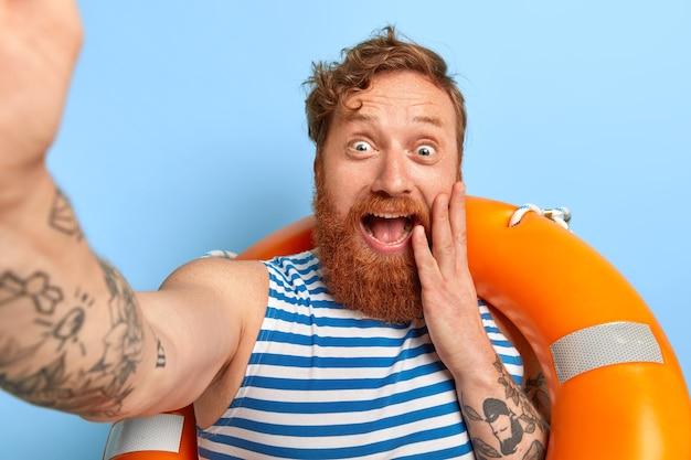 Homem ruivo engraçado e positivo tira uma foto de si mesmo, está de pé com uma bóia salva-vidas inflada, vestido com colete de marinheiro, tem barba espessa, aproveita férias incríveis na praia
