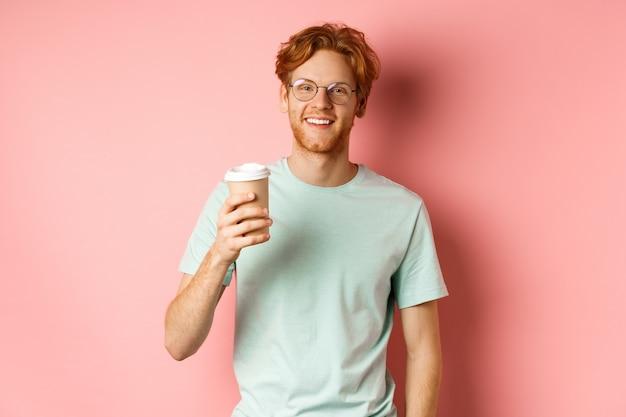 Homem ruivo feliz de óculos e camiseta, bebendo café e sorrindo, aproveitando a pausa para o almoço, segurando o copo para viagem, em pé sobre um fundo rosa.