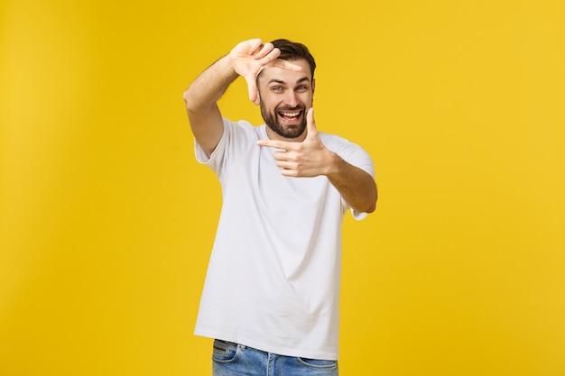 Homem ruivo irlandês bonito com barba de óculos sobre amarelo isolado sorrindo fazendo moldura com as mãos e dedos com cara feliz
