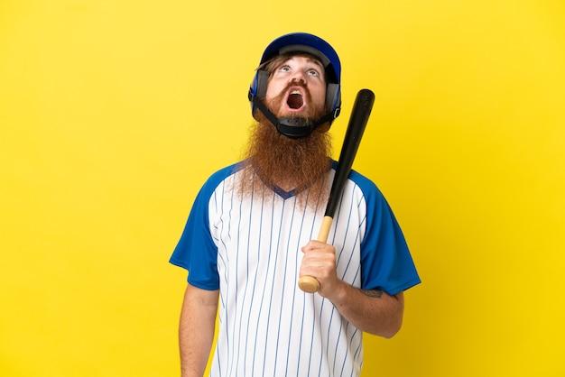 Homem ruivo jogador de beisebol com capacete e taco isolado em um fundo amarelo, olhando para cima e com expressão de surpresa