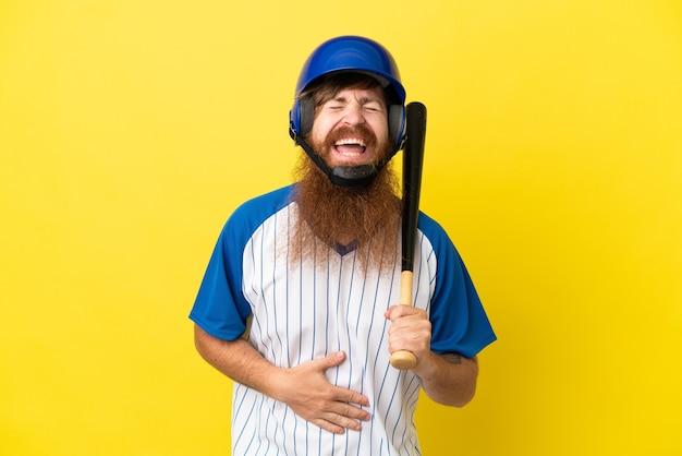 Homem ruivo jogador de beisebol com capacete e taco isolado em um fundo amarelo sorrindo muito