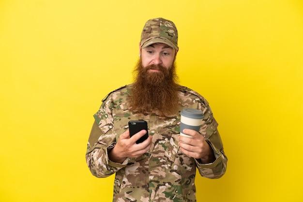 Homem ruivo militar isolado em um fundo amarelo segurando um café para levar e um celular