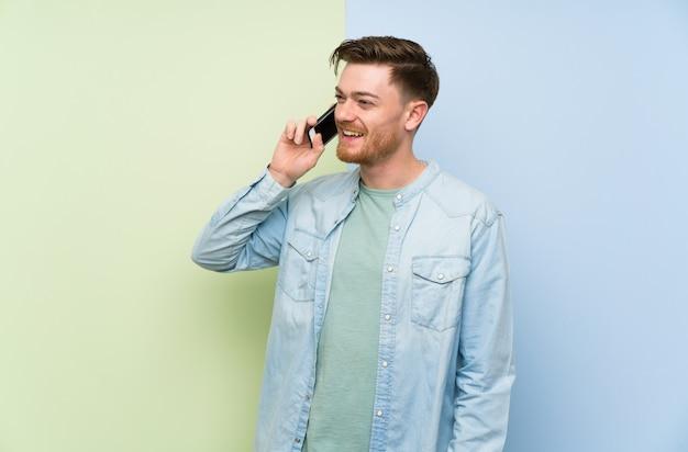 Homem ruivo muro colorido, mantendo uma conversa com o telefone móvel