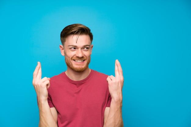 Homem ruivo na parede azul isolada com dedos cruzando