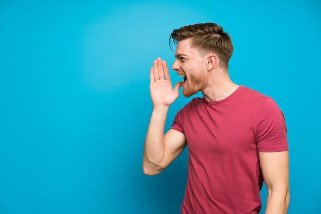 Homem ruivo na parede azul isolada, gritando com a boca aberta