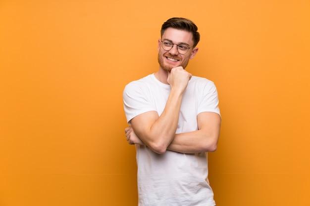 Homem ruivo na parede marrom com óculos e feliz