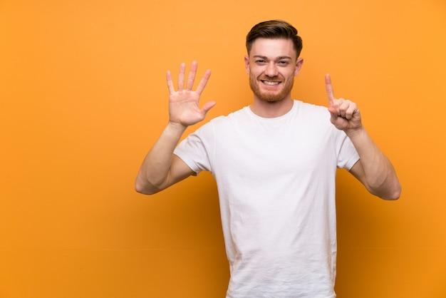 Homem ruivo na parede marrom, contando seis com os dedos