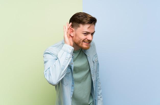 Homem ruivo ouvir algo, colocando a mão na orelha
