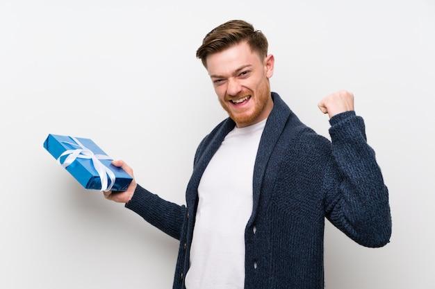 Homem ruivo segurando um presente