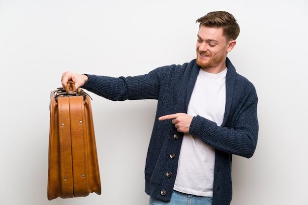 Homem ruivo segurando uma mala vintage