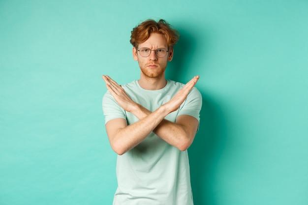 Homem ruivo sério e confiante, de camiseta e óculos, dizendo não, mostrando um gesto cruzado para impedi-lo, refutando ou recusando algo, em pé sobre um fundo turquesa.