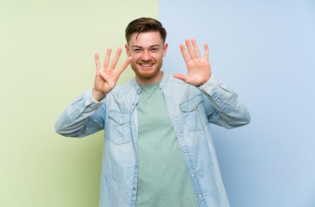 Homem ruivo sobre fundo colorido, contando nove com os dedos