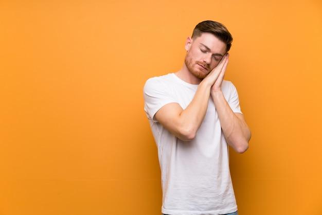 Homem ruivo, sobre, parede marrom, fazer, sono, gesto, em, dorable, expressão