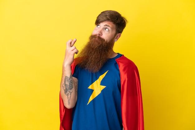 Homem ruivo super-herói isolado em fundo amarelo com os dedos se cruzando e desejando o melhor