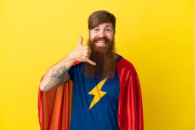 Homem ruivo super-herói isolado em fundo amarelo, fazendo gesto de telefone. ligue-me de volta sinal