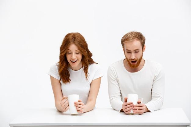 Homem ruivo surpreso, mulher olha borra de café