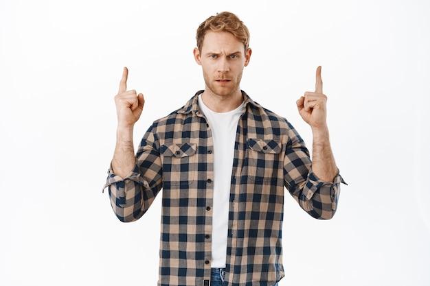 Homem ruivo suspeito descontente, tendo dúvidas, apontando o dedo para cima e parecendo cético ou duvidoso, expressa descrença, em pé sobre uma parede branca