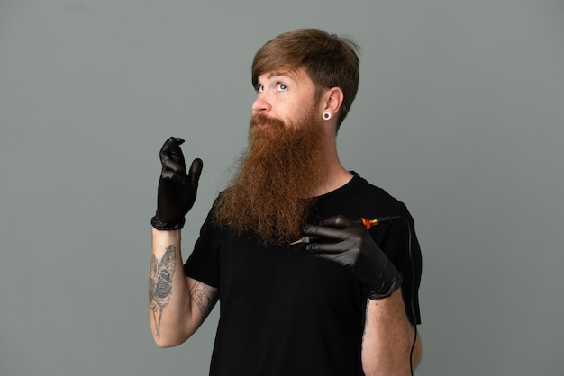 Homem ruivo tatuador isolado em um fundo azul com os dedos se cruzando e desejando o melhor
