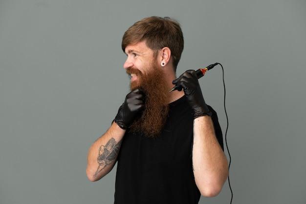 Homem ruivo tatuador isolado em um fundo azul, olhando para o lado e sorrindo