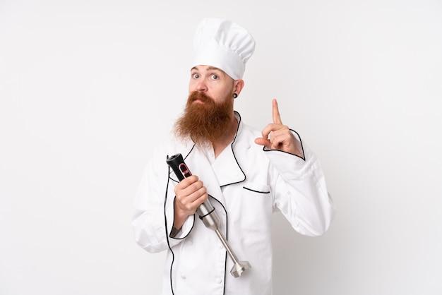Homem ruivo usando liquidificador mão sobre parede branca isolada, apontando com o dedo indicador uma ótima idéia