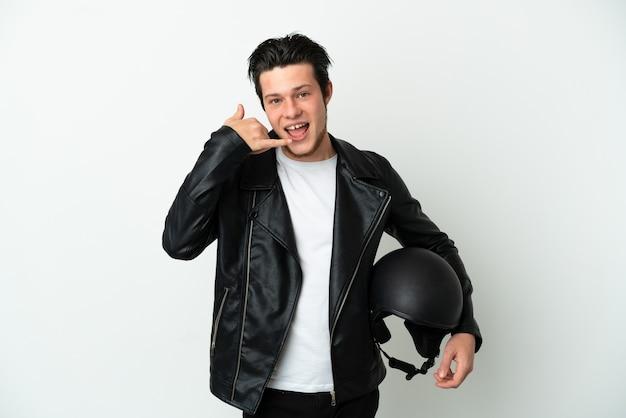 Homem russo com um capacete de motocicleta isolado no fundo branco, fazendo gesto de telefone. ligue-me de volta sinal