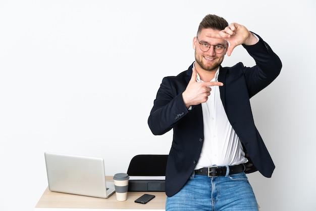 Homem russo em um escritório na parede branca, fazendo um quadro com os dedos