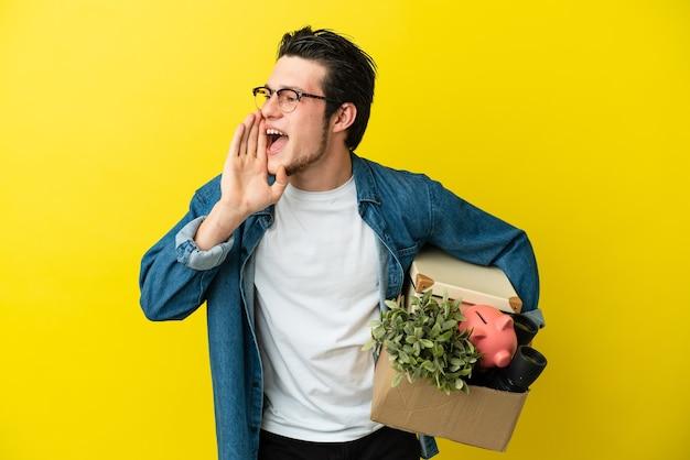 Homem russo se mexendo enquanto apanha uma caixa cheia de coisas isoladas em um fundo amarelo, gritando com a boca aberta para o lado