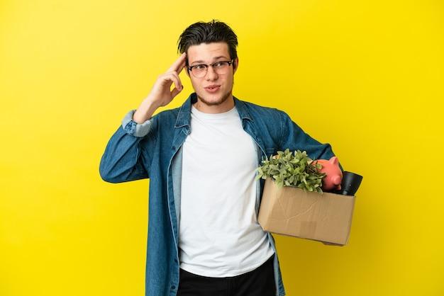 Homem russo se mexendo enquanto apanha uma caixa cheia de coisas isoladas em um fundo amarelo, tendo dúvidas e pensando
