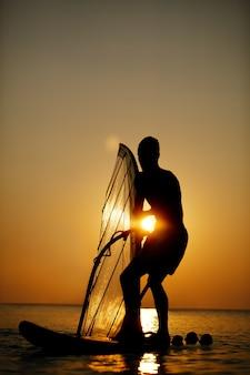 Homem, sailboarding, em, pôr do sol