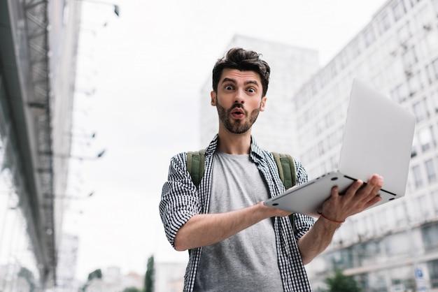 Homem saiu segurando laptop, compras on-line, em pé na rua da cidade