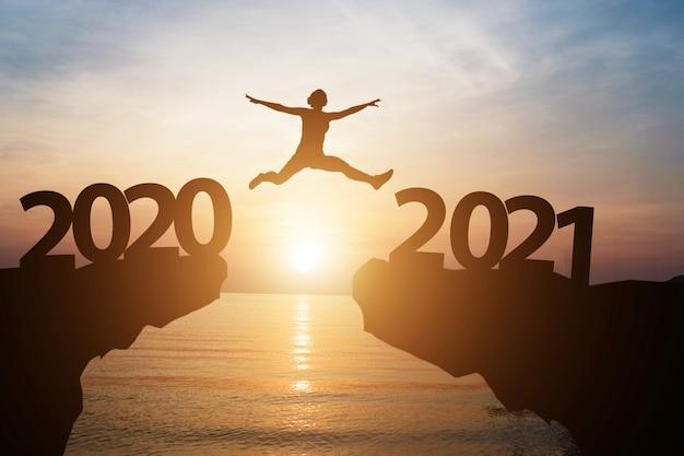 Homem salta do ano 2020 para 2021 com luz do sol e mar como pano de fundo