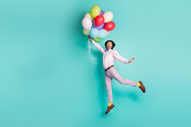 Homem saltitante descolado segurando balões de hélio coloridos se levantando e vestindo roupa formal isolada em fundo turquesa