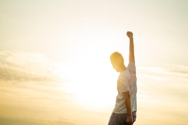 Homem saltitante. jovem louco está pulando no cume rochoso acima da paisagem. silhueta de homem pulando e céu pôr do sol elemento de design. efeito vintage.