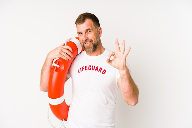 Homem salva-vidas sênior isolado na parede branca alegre e confiante, mostrando o gesto de ok.