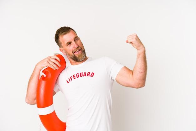 Homem salva-vidas sênior isolado na parede branca, levantando o punho após uma vitória, o conceito de vencedor.