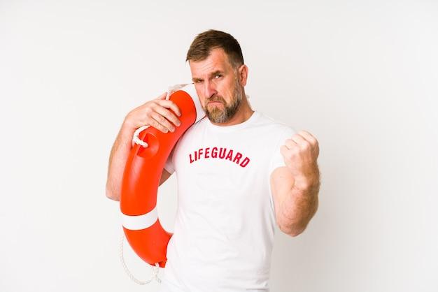 Homem salva-vidas sênior isolado na parede branca, mostrando o punho, expressão facial agressiva.