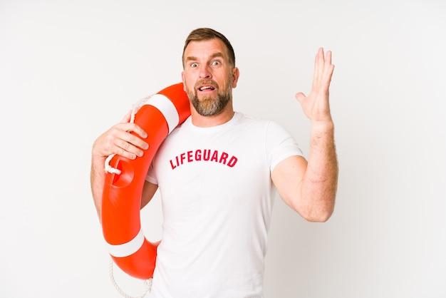 Homem salva-vidas sênior isolado no fundo branco, recebendo uma agradável surpresa, animado e levantando as mãos.