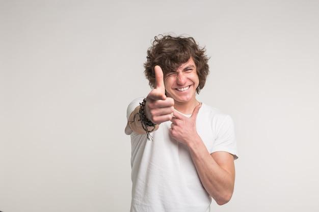Homem sardento emocional em fundo branco mostra o dedo na câmera.
