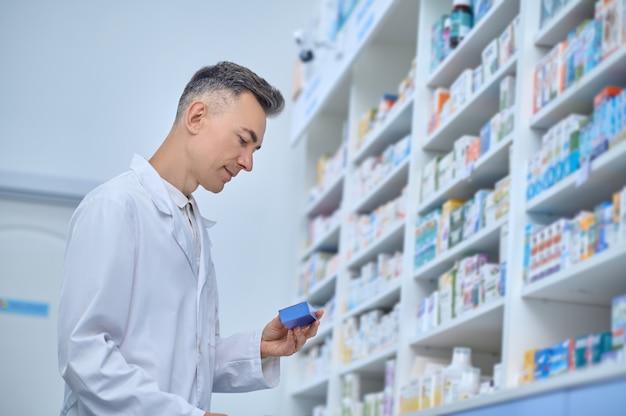 Homem satisfeito de jaleco revisando medicamentos na farmácia