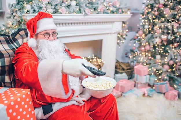 Homem satisfeito e feliz em traje de papai noel se senta e usa o controle remoto. ele tem uma tigela de pipoca na outra mão. há lareira e árvore de natal por trás do homem.