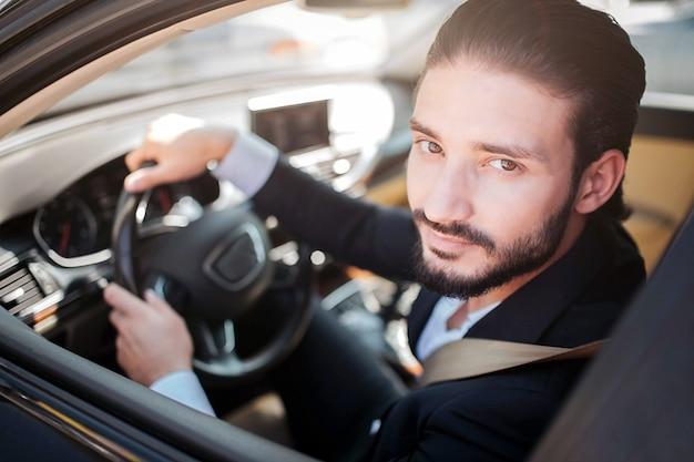 Homem satisfeito e feliz sentado no carro e posando. ele olha para a câmera e sorri um pouco. cara barbudo mantém as mãos no volante.
