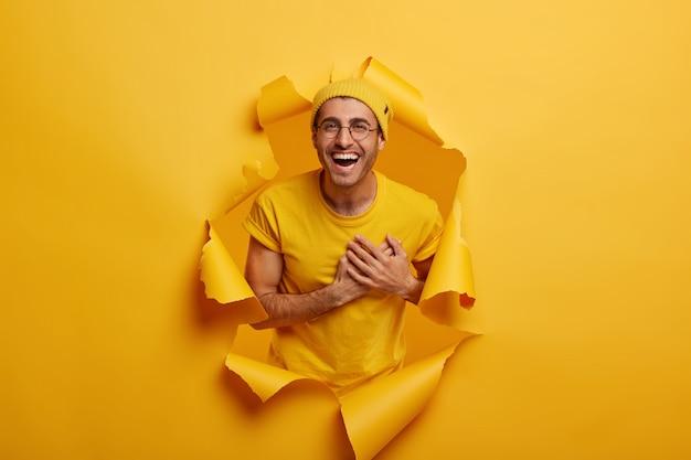 Homem satisfeito em pé no buraco do papel, mantém as mãos perto do coração, expressa gratidão