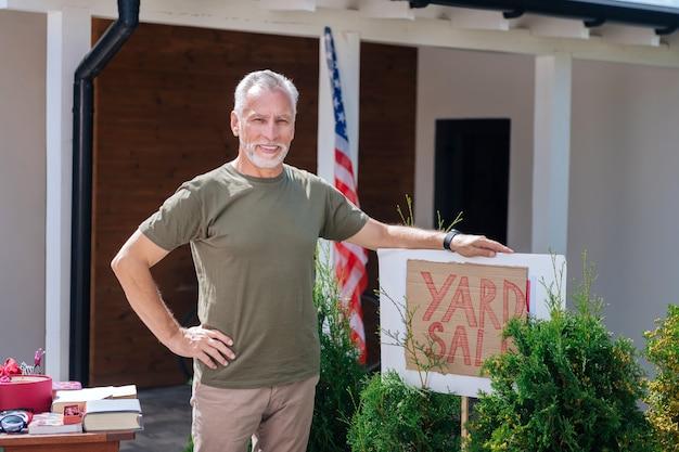 Homem satisfeito. homem barbudo e sorridente, vestindo uma camisa cáqui escura, sentindo-se satisfeito após organizar uma incrível liquidação de garagem