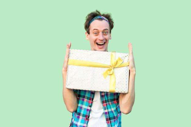 Homem satisfeito jovem hippie em t-shirt branca e camisa quadriculada, mostrando o presente com a boca aberta, olhos grandes e sorriso cheio de dentes, olhando para a câmera. interior, isolado, foto de estúdio, fundo verde