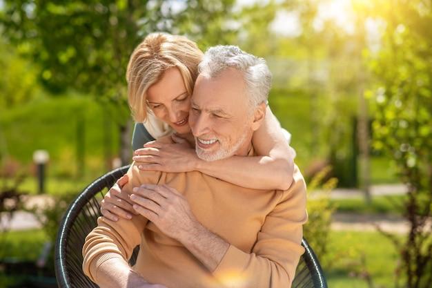 Homem satisfeito sendo abraçado por uma mulher por trás