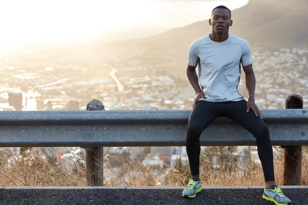 Homem saudável de pele negra, descansa em uma placa de trânsito, usa roupas casuais, olha com confiança para a câmera, modela a vista panorâmica com montanhas e cidade, leva estilo de vida saudável. treinamento físico