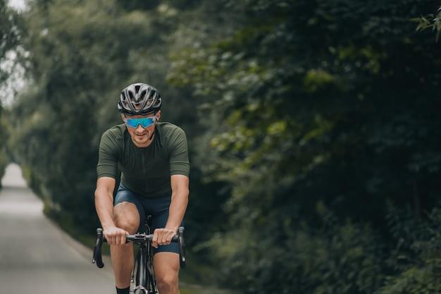 Homem saudável e em forma andando de bicicleta na estrada em meio à natureza verde